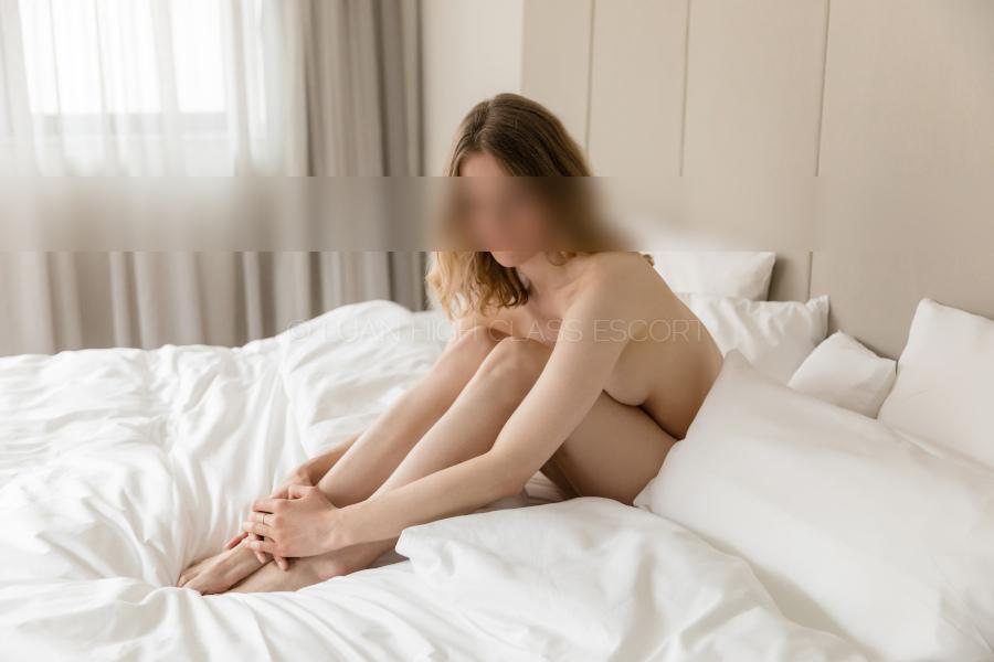 Escort Lady sitzt nackt im Bett