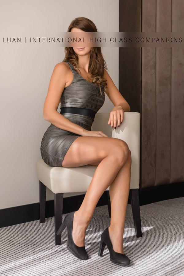 Escortgirl sitzt in engem Kleid auf dem Stuhl