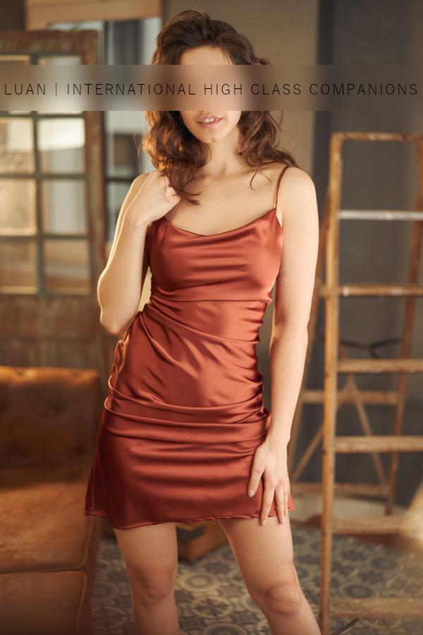Escortdame in einem elegantem Abendkleid moechte mit einem Gentleman ausgehen